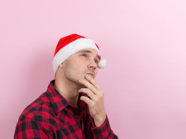 Эмоции на лице, задумчивость, рефлексия, план, идея. человек в клетчатом кролике и рождественской красной шляпе