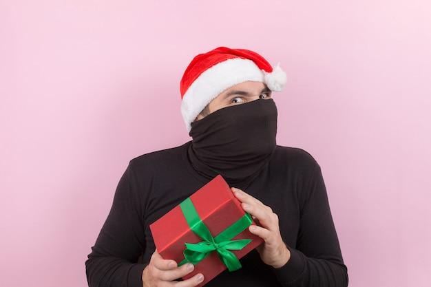 赤い帽子をかぶった泥棒が、誰かのクリスマスプレゼントを盗みました。怒った性格、否定的な人間の感情。ピンクの背景、コピースペース。