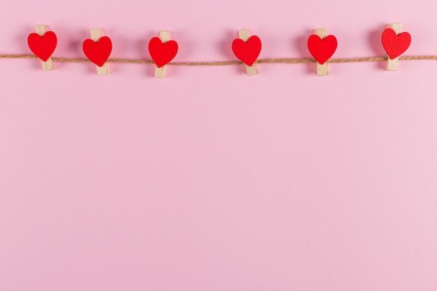 ピンクの背景のジュートロープに洗濯はさみで赤いハートが開催されます。コピースペース。
