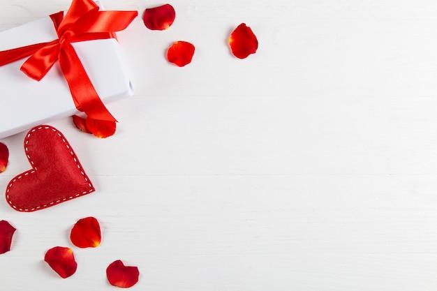 テーブルの上に赤いリボンハンドメイドハートと白いパックギフト。