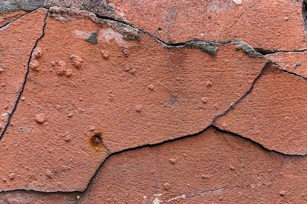 古い赤いひびの入った壁