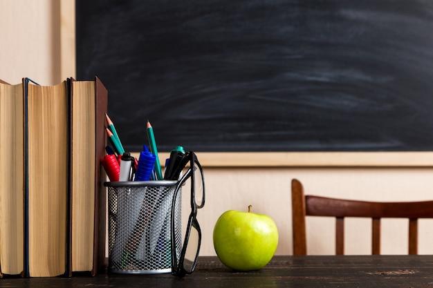 本、リンゴ、ペン、鉛筆、チョークボードに対する木製のテーブルの上のグラス。