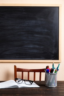 本、ペン、鉛筆、チョークボードに対する木製のテーブルの上のグラス。