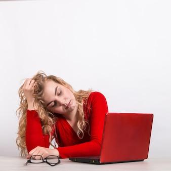 赤、白のコンピューターでリモートで働く女性。