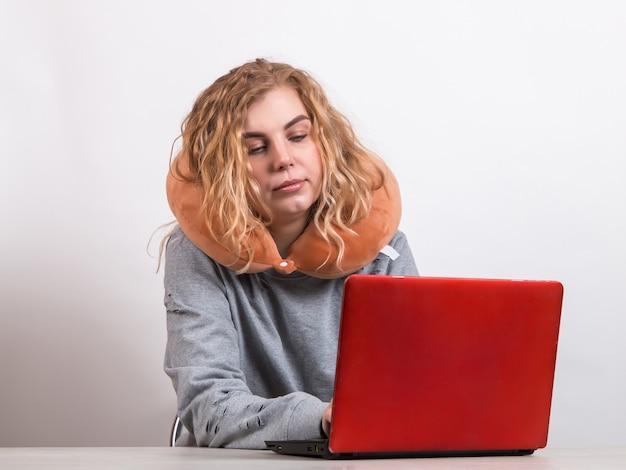 女性は白で首の周りに枕を置いてコンピューターで働いています。