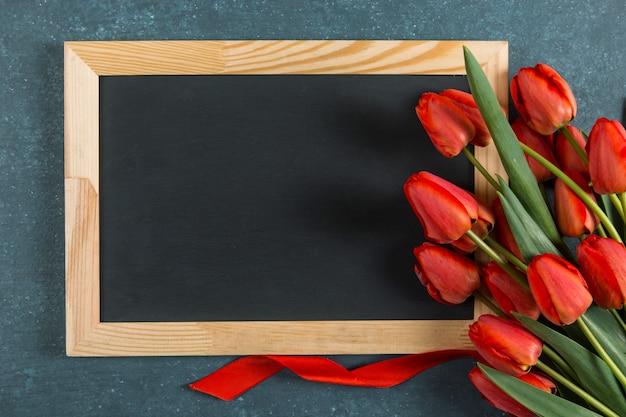 赤いチューリップと青の黒板、教師の日のポストカード用の空白。コピースペース。
