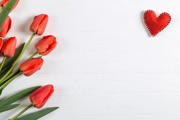 赤いチューリップと白いテーブルの心、はがきの空白。コピースペース。