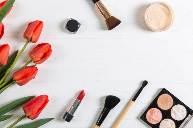 Красные тюльпаны и косметика на белом столе, пустой. копировать пространство