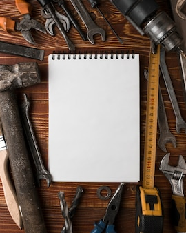 Многие удобные инструменты и пустой блокнот на деревянном столе, вид сверху