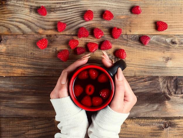 Целебный чай с малиной и ягодами на столе. чашка в руках девушки. борьба с простудой зимой естественными методами.