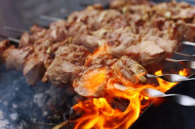 夏の自然の中でバーベキュー。石炭、健康食品、クローズアップの煙で豚肉。