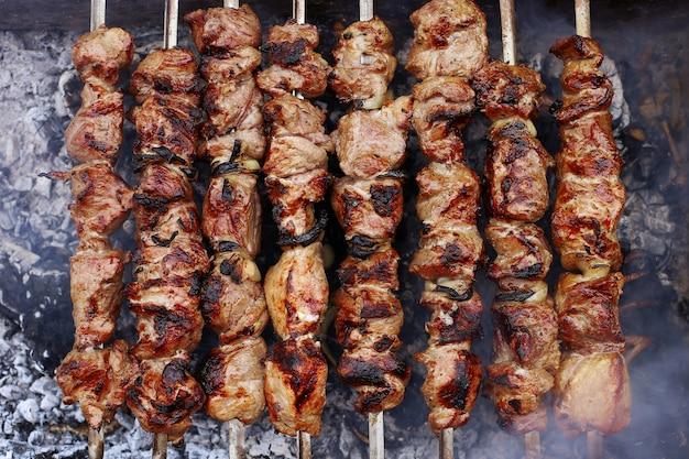 夏の自然の中でバーベキュー。石炭、健康食品、クローズアップ、トップビューで煙の豚肉。