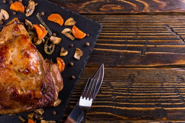太ももの七面鳥は、黒い石のボード上のスパイスとオーブンで焼きました。健康食品。感謝祭のディナー。
