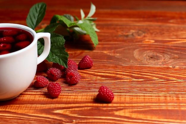 Чай с малиной и ягодами рядом с чашкой, на деревянном столе винтаж.