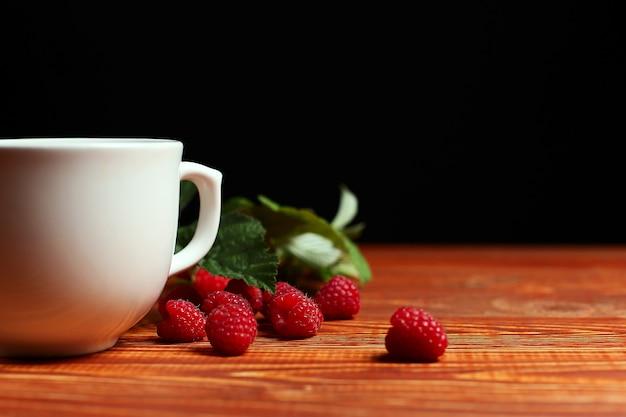 木製のビンテージテーブルの上のカップの横にラズベリーとベリーのお茶。