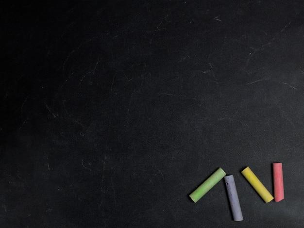 黒板背景に色付きのクレヨン。