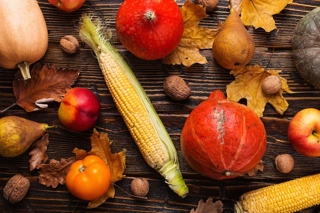 さまざまな野菜、カボチャ、リンゴ、梨、ナッツ、トマト、トウモロコシ、木製の背景に黄色の乾燥葉。秋の気分、平干し。収穫。