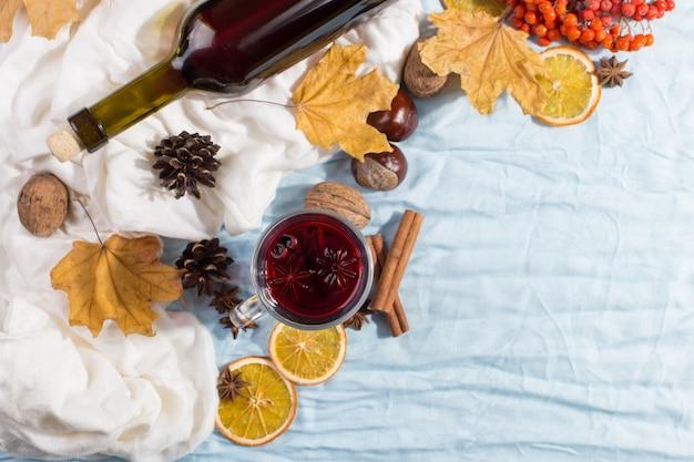 スパイス、ボトル、乾燥葉、テーブルの上のオレンジとホットワインのカップ。秋の気分、寒さ、コピースペース、朝の光で暖かく保つ方法。