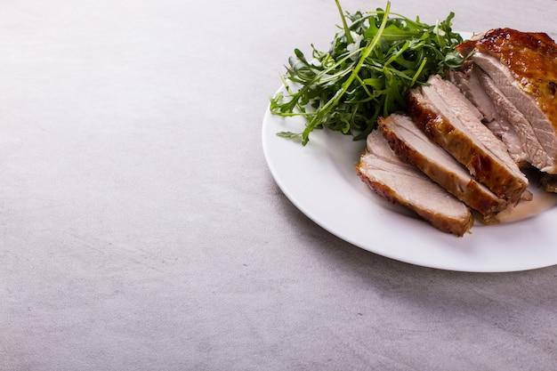 太ももの七面鳥は、卓上の白い皿の上のスパイスとオーブンで焼きました。健康食品。感謝祭のディナー。
