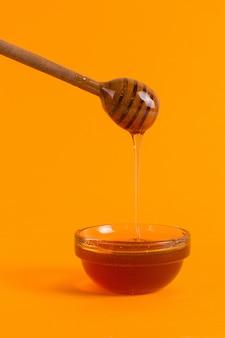 黄色の背景に蜂蜜と小さな瓶の棒。