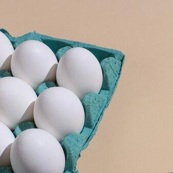 パステル調の背景のトレイに白い卵。