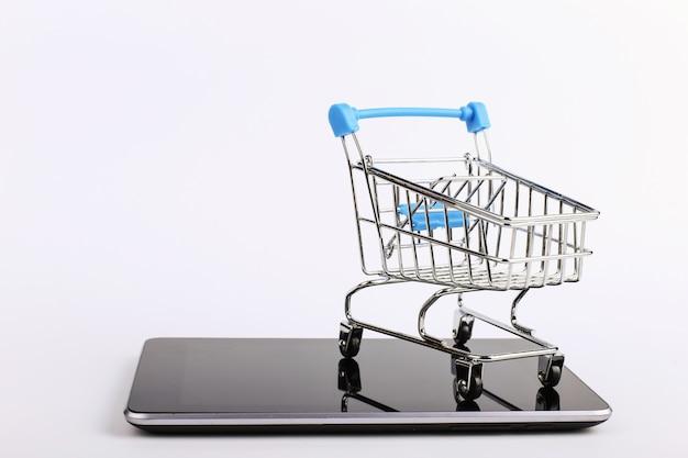 ショッピングカートは、スマートフォンの上に立ちます。オンライン販売の概念
