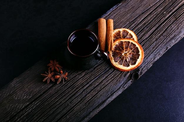 暗いキッチンカウンターの上にコーヒー、スターアニス、シナモン、乾燥オレンジ、コーヒー豆