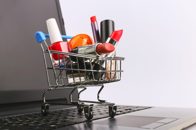 化粧品の買い物カゴはラップトップ上にあります。オンライン販売の概念