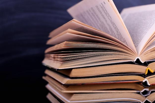 開いた本は机の上に積み重ねられ、黒板を背景にしています