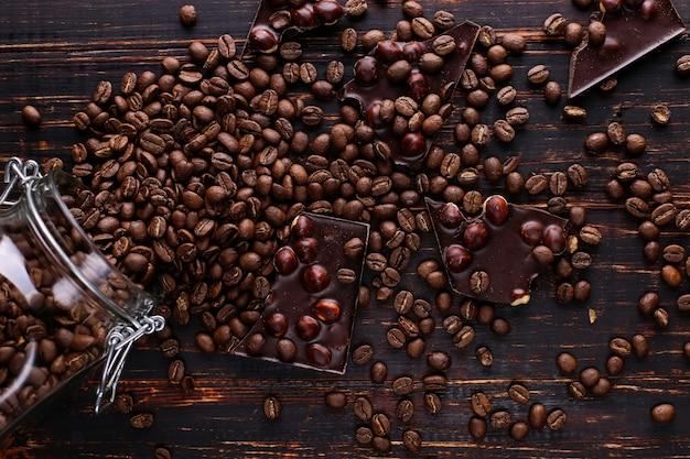 Чонсервная банка кофе, разбросанных зерен и черного шоколада на деревянном столе.