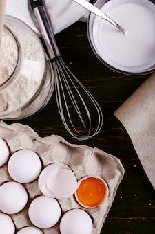 小麦粉、ケフィアの卵、木製テーブルの上の泡立て器。パンケーキ用の混合物の準備、調理。
