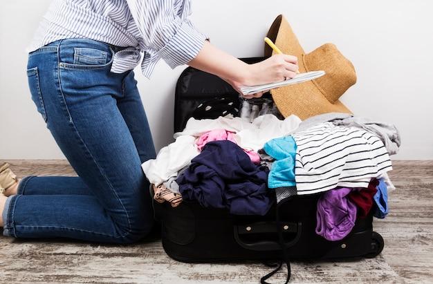 若い女の子は何気なく黒いスーツケースをパック
