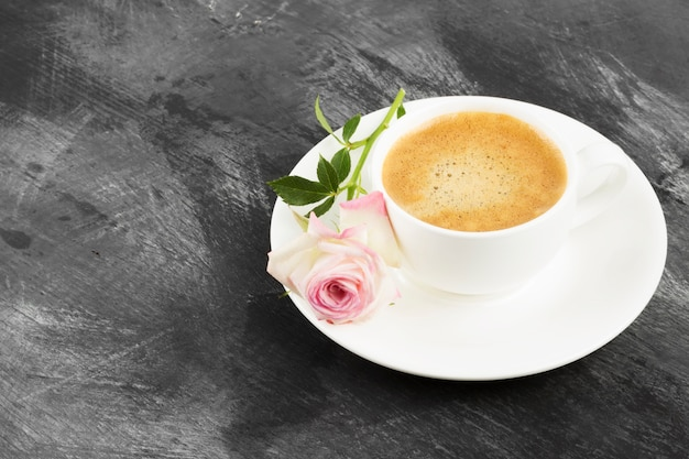 白いカップと暗い背景にピンクのバラのエスプレッソコーヒー。コピースペース。食品の背景