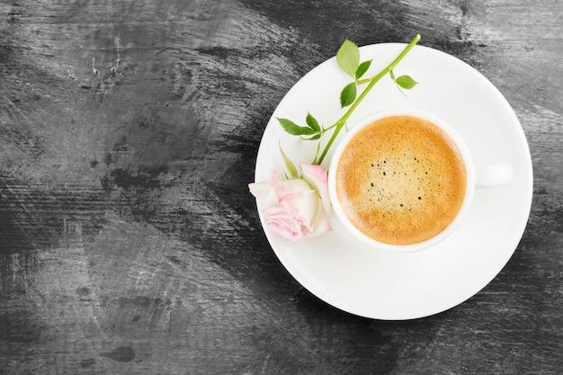 白いカップと暗い背景にピンクのバラのエスプレッソコーヒー。トップビュー、コピースペース。食品の背景