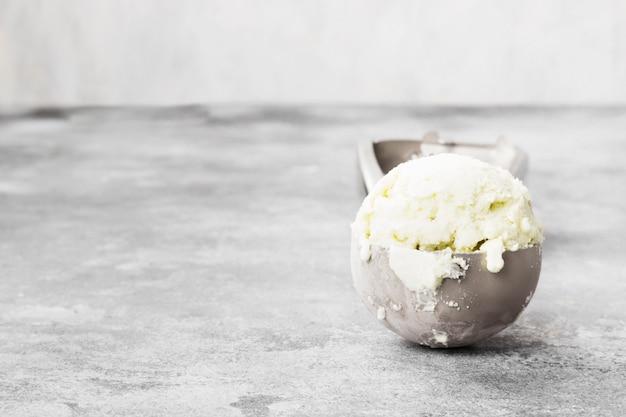 Мятное мороженое в ложке на сером фоне.
