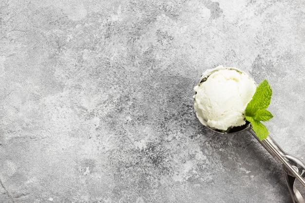 灰色の背景にスプーンのミントアイスクリーム。