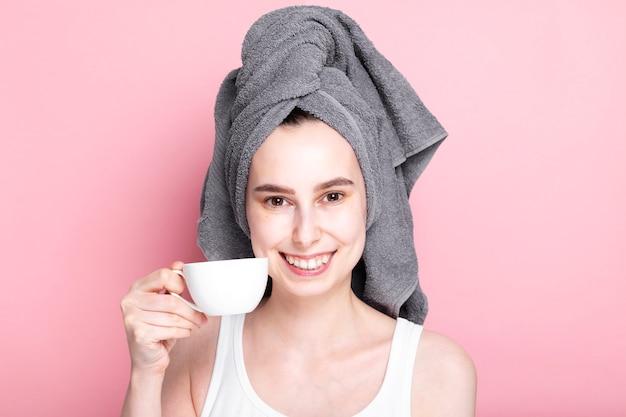 Молодая женщина с полотенцем на голове держит чашку кофе в руке и улыбается на розовом пространстве. утренняя рутина, приятно проведенное время, медленный сбор
