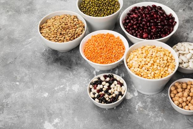 Ассортимент бобов (красная чечевица, зеленая чечевица, нут, горох, красная фасоль, белая фасоль, микс фасоли, фасоль мунг) на сером пространстве. копировать пространство пищевое пространство