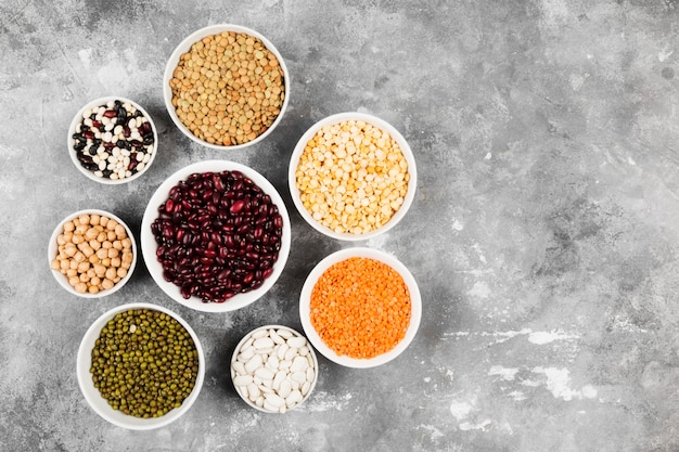Ассортимент бобов (красная чечевица, зеленая чечевица, нут, горох, красная фасоль, белая фасоль, микс фасоли, фасоль мунг) на сером пространстве. вид сверху, скопируйте пространство. пищевое пространство