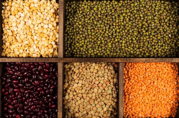 Ассортимент бобов (красная чечевица, зеленая чечевица, нут, горох, красная фасоль, белая фасоль, микс фасоли, фасоль мунг). вид сверху. пищевое пространство