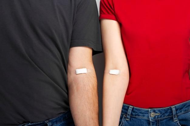 Донорство крови. мужчина в сером и женщина в красной футболке с наклеенными на руки пятнами после сдачи крови
