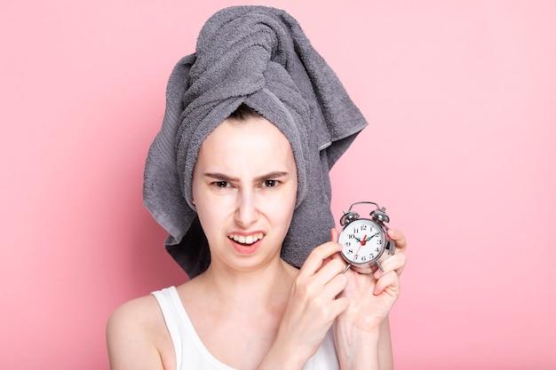 ピンクに寝坊した目覚まし時計に不満の若い女の子のショー