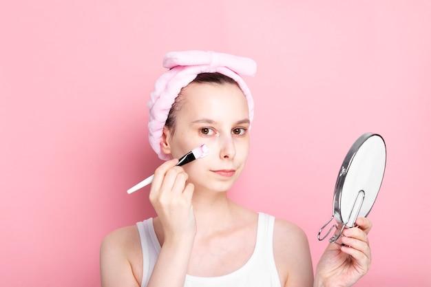 Молодая девушка наносит косметическую маску кисточкой