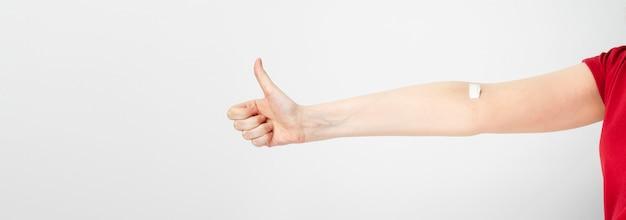 Молодая девушка показывает большой палец вверх, вторая рука проклеена патчем после сдачи крови