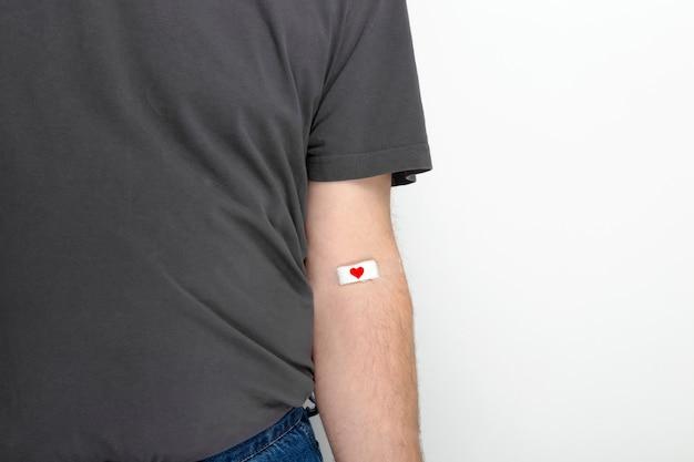 Рука человека приклеена патч с красным сердцем после сдачи крови