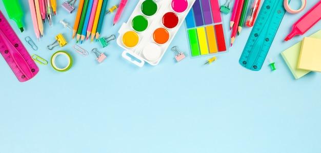 青の背景に様々な学校のオフィスと絵画用品。学校のコンセプトに戻る。