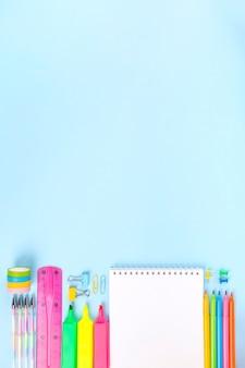 青の背景に様々な学校事務用品。学校のコンセプトに戻る。