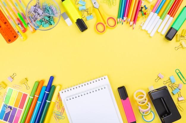 黄色の背景に様々な学校のオフィスや絵画用品。学校のコンセプトに戻る。
