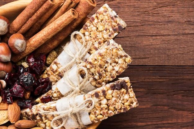 Зерновые батончики с орехами, ягодами и корицей на деревянном фоне