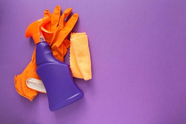 洗剤と洗浄剤、スポンジ、ナプキン、ゴム手袋、紫色の背景。上面図。コピースペース